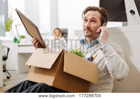 Sharing my bad news. Fired puzzled upset employee sitting and holding the box with his personal documents while expressing sadness and having conversation on the phone