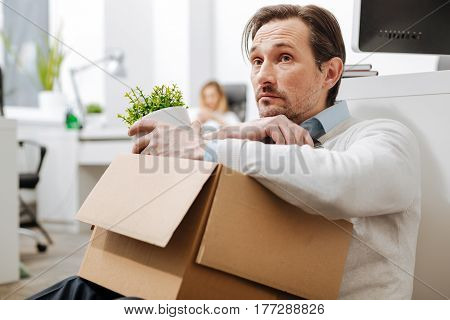 Feeling lonely. Fired melancholy upset man sitting on the floor in the office and holding the box with his personal stuff while expressing sadness