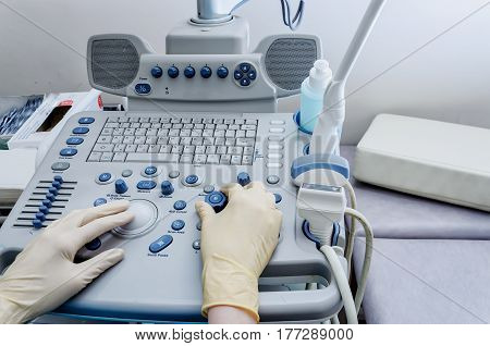 The doctor's hands on the ultrasound machine in clinic