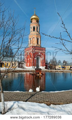 red Bell tower of the ascension of David Desert Chekhov district of Russia, historical and cultural monuments of Christianity with reflection in pond