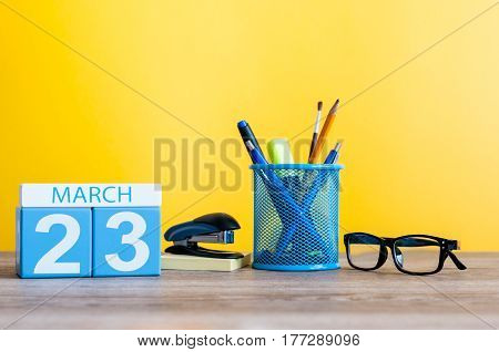 March 23rd. Day 23 of month, calendar on light yellow background, workplace with office suplies. Spring time, empty space for text.