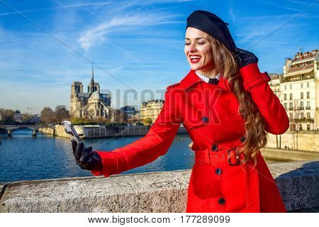 Woman On Embankment In Paris, France Taking Selfie With Phone