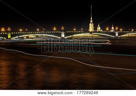 Night of St. Petersburg on the Neva, the Peter and Paul fortress across the bridge and traces of light from passing boats. Long-term exposure.