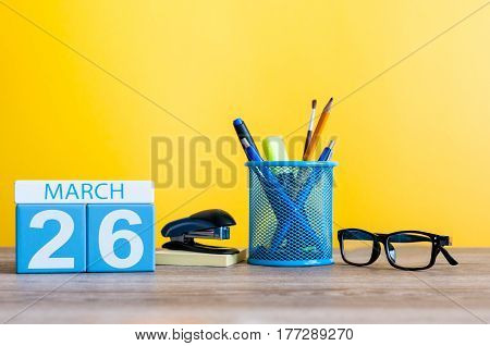 March 26th. Day 26 of month, calendar on light yellow background, workplace with office suplies. Spring time, empty space for text.