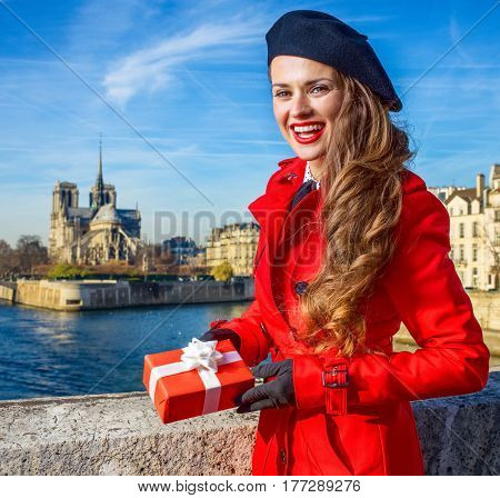 Woman On Embankment In Paris Showing Christmas Present Box