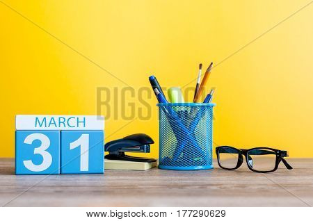 March 31st. Day 31 of month, calendar on light yellow background, workplace with office suplies. Spring time, empty space for text.