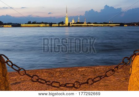 St. Petersburg in the evening on the banks of the Neva, the Peter and Paul fortress with lights, across the river