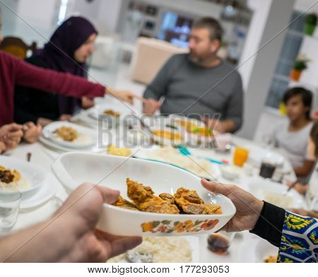 Family gathering eating meal around kitchen table