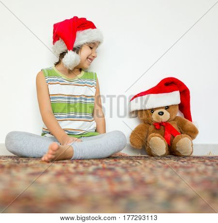 Child with Santa hat playing with Teddy bear