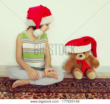 Little kid in Santa hat with cute teddy bear waiting at home for New year