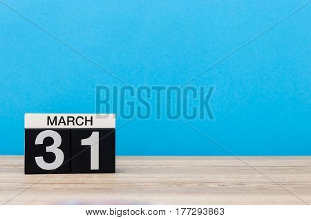 March 31st. Day 31 of month, wooden calendar on light blue background. Spring time, empty space for text.