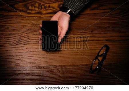 Man hand keep smart phone on a wooden table. Phone and glasses. Business situation. Coffee break