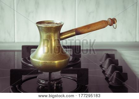 Old turkish copper pot for brewing coffee on stove. Early breakfast. Turkish method of brewing coffee.