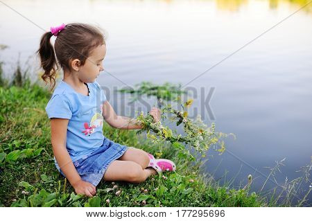 Child girl lets on the river a wreath of wild flowers. Celebration of Ivan Kupala. Midsummer day