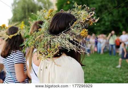 Girls with wreaths of wild flowers lead round dance on the background of people. Feast of Ivan Kupala. Midsummer day. Easter