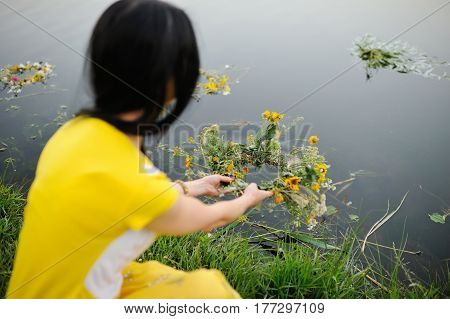 A girl in a yellow dress launches a wreath of wild flowers along the river