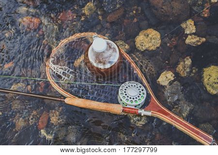 Fishing rod net and growler of beer in the river.