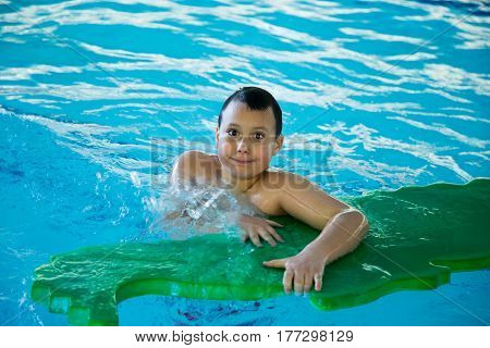 Young boy in a swimming pool with a floating pool toy.
