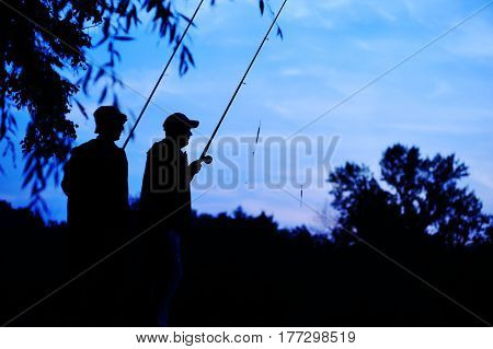 Silhouettes of two fishermen with fishing rods on nature background and blue sky. Fishing