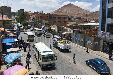 Potosi Bolivia - November 30 2013: View of a busy street in the city of Potosi with the Cerro Rico on the background. Potosi is one of the highest cities in the world and it was the major supply of silver for Spain during the colonial era.