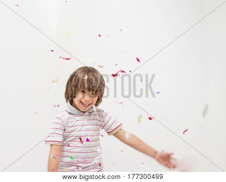 Cute little boy celebrating for party on white wall copy space