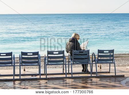 Nice, France - 25 February, An elderly lady is reading on the waterfront, 25 February, 2017. People and tourists having a rest on the Cote d'Azur.