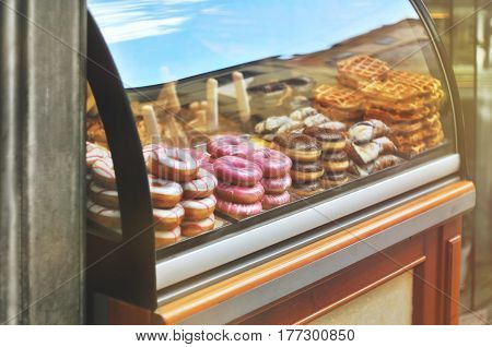 Rich variety of italian cookies donuts wafer in showcase of typical pastry shop in the street of Florence at a sunny day with a sky reflection on display window