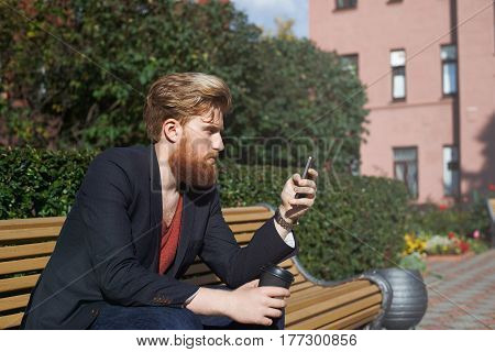 Concentrated bearded hipster talking in the internet by phone. High technology concept. Man surf social network for search new job. Sun effect. Male sit on bench in industrial part of the city
