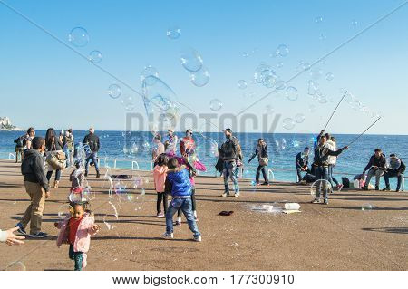 Nice, France - 25 February, Children and soap bubbles, 25 February, 2017. People and tourists having a rest on the Cote d'Azur.