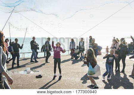 Nice, France - 25 February, A long soap bubble over people, 25 February, 2017. People and tourists having a rest on the Cote d'Azur.