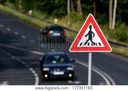 Pedestrian crossing, traffic sign and cars on road