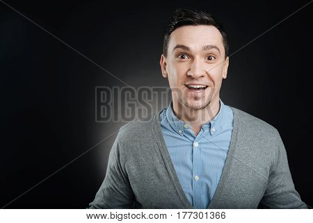 Be shocked. Closeup portrait of handsome male person, looking wondered keeping his eyes and mouth wide opened standing isolated on black background