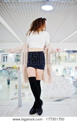 Young Curly Model Girl Posed On Mini Skirt At Large Shopping Center Near Glass Railings.