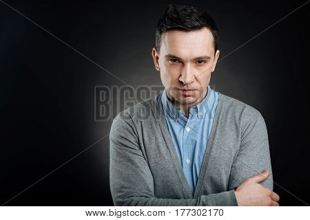 Do not irritate me. Serious brunette male person wearing casual clothes crossing hands on chest while pressing lips