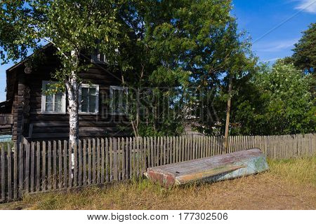Northen Russian Village. House with trees and boat