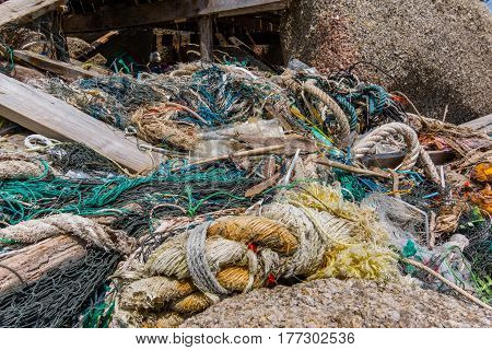 Plastic pollution among the stones on a tropical shore Rubbish ropes and cords. Haad Rin Koh Pangan Thailand - April 30 2016