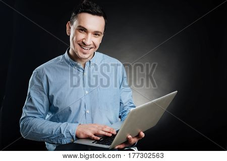 Easy task. Attractive smiling office worker wearing blue shirt using computer while posing on camera