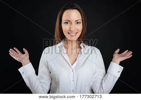 It is me. Positive delighted female wearing white shirt keeping smile on her face while standing over black background