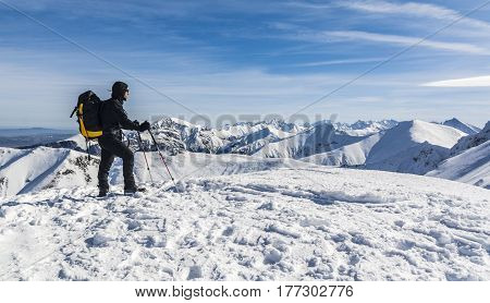 Tourist From Trekking Poles And Backpack In The Winter In The Mountains.