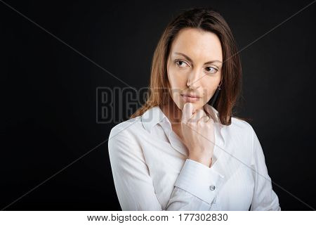Look for idea. Thoughtful female wearing white shirt keeping right hand on her chin while standing in semi position over black background