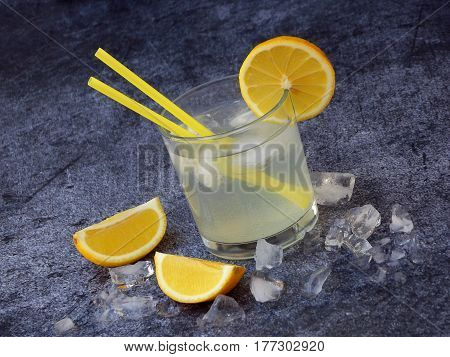 One Glass Of Cold Homemade Lemonade With Lemon Slices, Ice Cubes And Straws On Dark Background. Copy