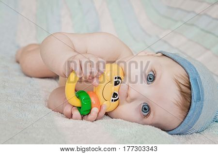 Smiling Newborn Baby Lying On Bed With Toys