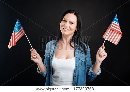 My dream. Pleased female wearing jeans shirt smiling and keeping two flags in her hands