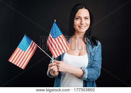 Preparation for celebration. Attractive black-haired woman wearing jeans shirt and white T-shirt keeping smile on her face and posing with two flags in her hands
