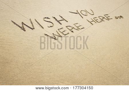 Wish you were here written in the sand on the beach.