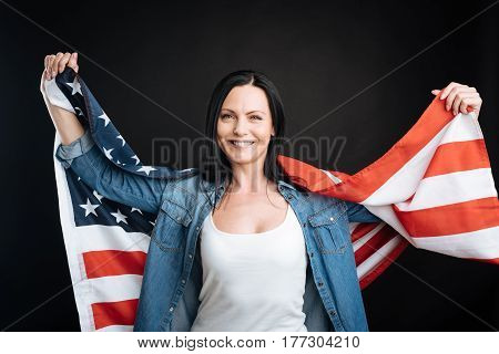 Look in future. Attractive black-haired female wearing jeans shirt and white T-shirt holding her arms in the air while standing over black background