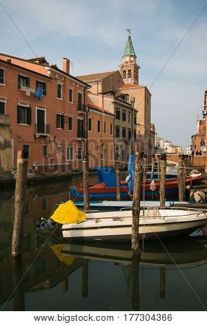 View over channel with boats, houses and reflections in Chioggia