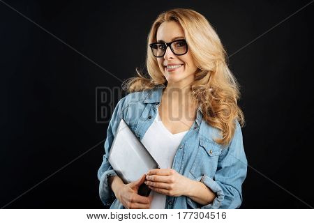 Be responsible. Attractive female wearing glasses looking straight on camera while keeping smile on her face, isolated on black
