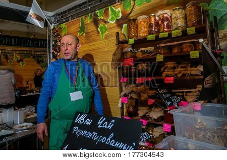 Moscow, Russia - February 25, 2017: Seller of home produced pickled mushrooms at the fair on VDNKh next to a rack with jars