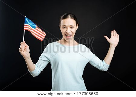 My changes. Smiling female keeping her mouth opened posing with flag in right hand standing over black background